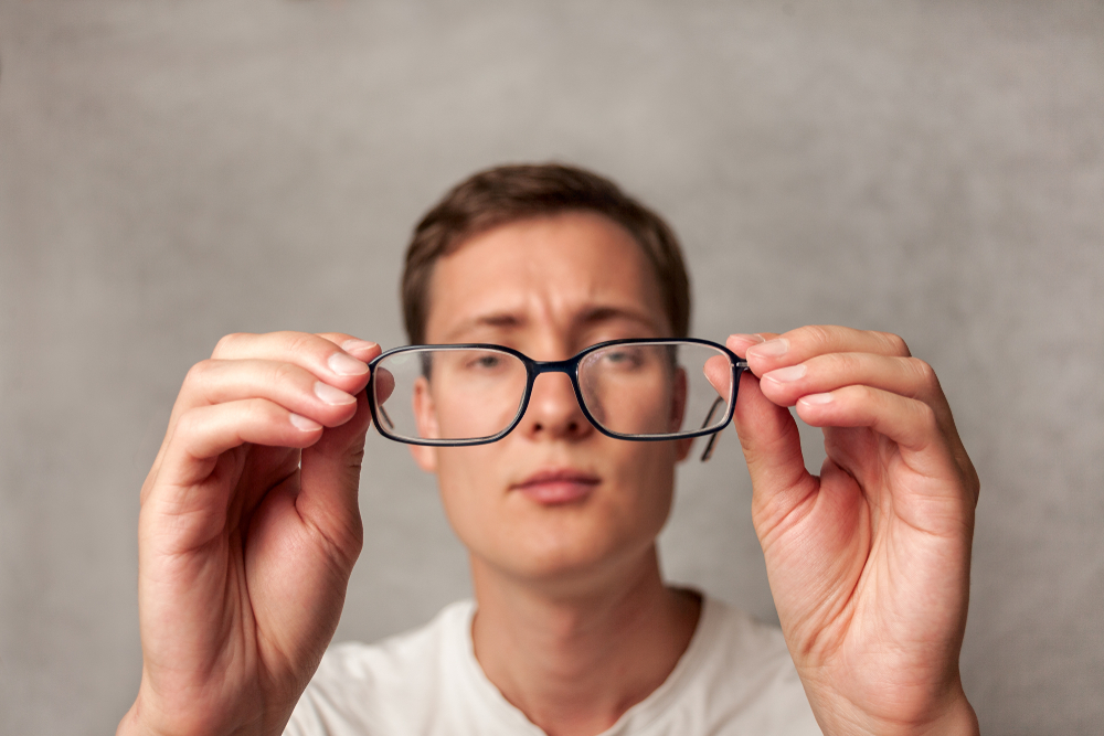 Дечко кој држи очила во раце оддалечени од него. Висока диоптрија.