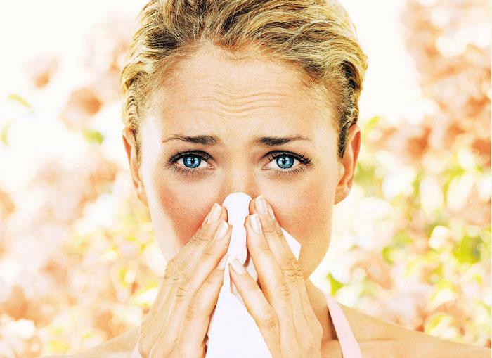 Девојка која кива со марамица поради алергија на очи.